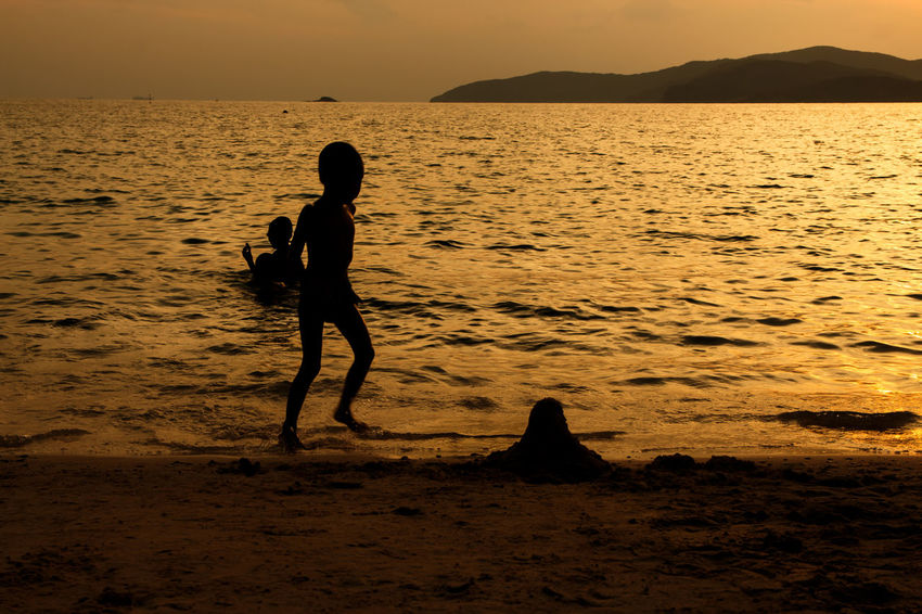 silhouette of people at the beach,The beauty of natural light at sunset. Water Sunset Real People Sea Sky Beauty In Nature Silhouette Beach Lifestyles Land Scenics - Nature Leisure Activity Nature Tranquil Scene Tranquility Men People Two People Orange Color Outdoors Silhouette Happiness Happy Holiday Relaxing Children Women Man Romantic Orange Clouds And Sky Love Family Summer Sunrise Boy Freshair Freedom Fun