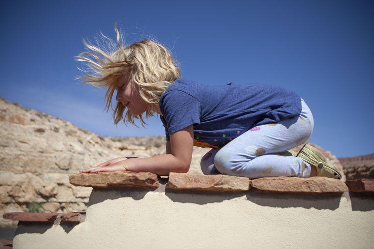 Full length of teenage girl sitting on sand