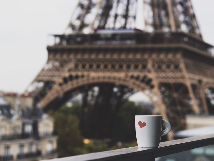 Coffee Cup On Railing With Eiffel Tower Seen In Background