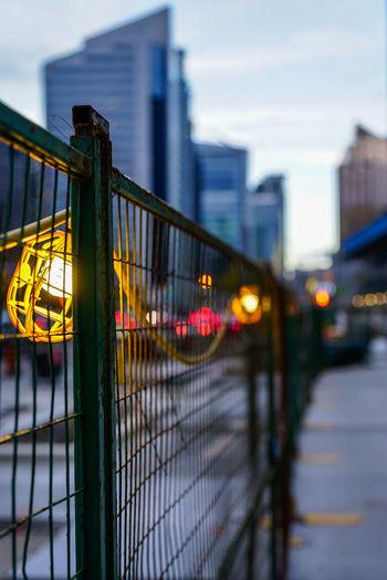 Illuminated city against sky seen through fence