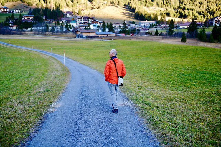 Rear view of man walking on road amidst grassy field