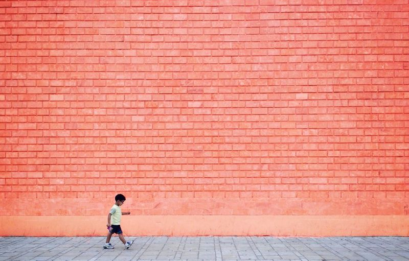 Showcase: February little little boy in a big big world Boy Child Colored Wall Orange Orange Color Minimalism Minimal Minimalobsession Minimalist Negative Space Monochrome Passing By In Front Of A Wall Hello World Big World, Little People Timing The Street Photographer - 2016 EyeEm Awards