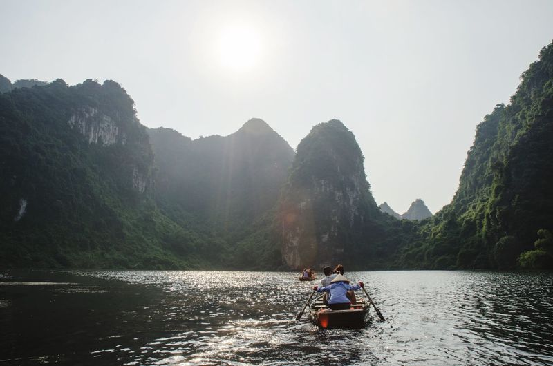 People sitting on boat in river against sky