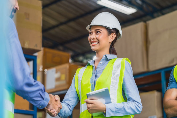 Smiling engineer shaking hand with co worker at warehouse