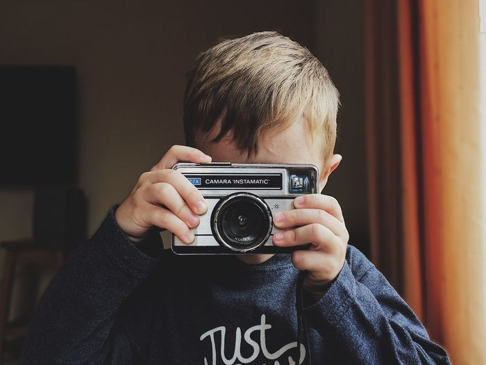 Camera - Photographic Equipment Photography Themes Holding Real People One Person Leisure Activity Lifestyles Technology Activity Photographing Retro Styled Indoors  Men Casual Clothing Photographic Equipment Headshot Photographer Portrait Digital Camera Front View