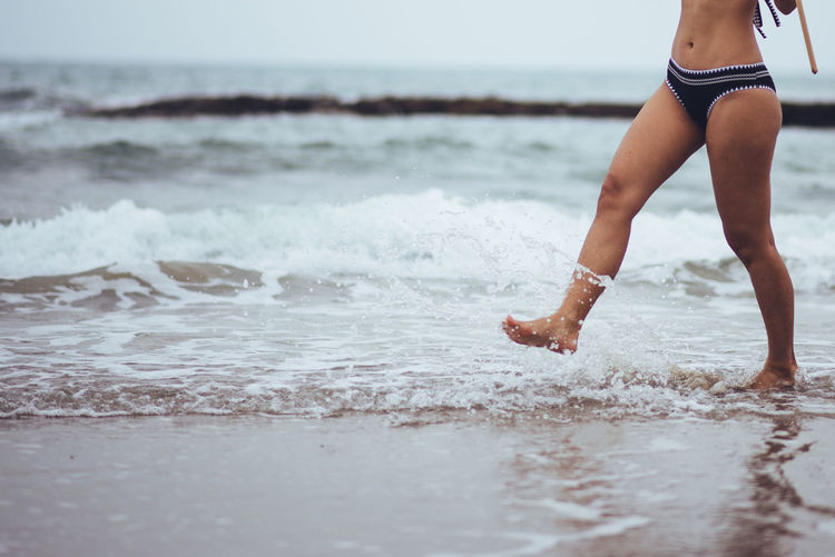 Sea One Person Lifestyles Water Beach Land Real People Leisure Activity Motion Wave Day Nature Selective Focus Human Body Part Holiday Beauty In Nature Sky Standing Outdoors
