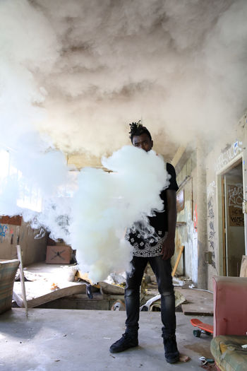 Portrait of man standing with smoke in abandoned home