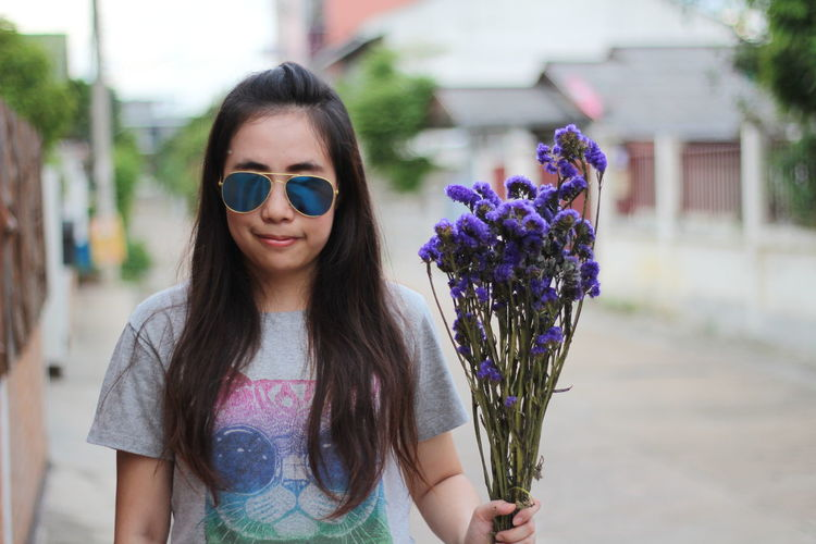 Portrait Of Woman Wearing Sunglasses While Holding Purple Flowers On Footpath