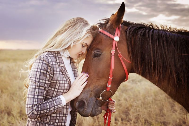 Profile view of young woman standing face to face with horse on field