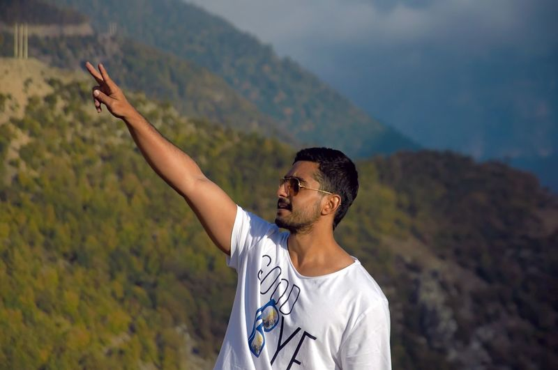 Young man gesturing peace sign while standing against mountains