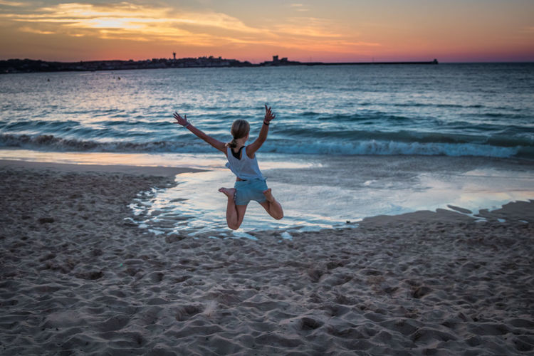 Full length of woman jumping at beach against sky during sunset