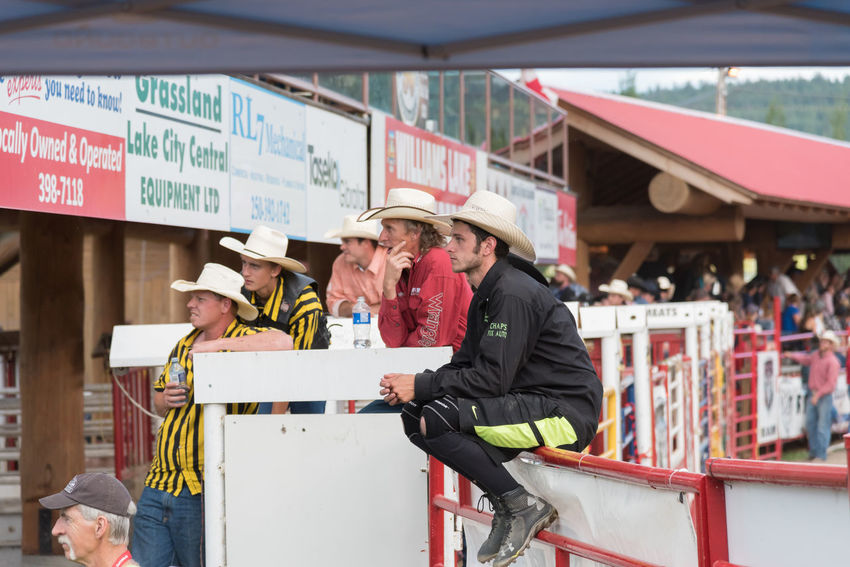 Williams Lake, British Columbia/Canada - July 1, 2016: group of cowboys sit by the chutes watching the Mountain Race at the 90th Williams Lake Stampede, one of the largest stampedes in North America 90th Williams Lake Stampede Anxious  Behind The Scenes British Columbia, Canada Cowboys Mountain Race Rodeo Travel Candid Chutes Competition Country Western Cowboy Hat Documentary Editorial  Group Men Outdoors People Professional Rodeo Stampede Stampede Grounds Team Tourism Watching