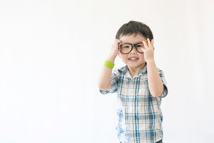 Cute little Asian boy White Background Child Portrait Eyeglasses  Smiling Childhood Happiness Standing Studio Shot Intelligence Children Preschooler Nerd
