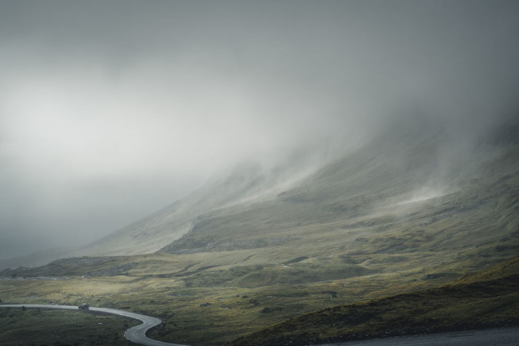 Moody weather. Location: Norðradalur, Faroe Islands Equipment: Fujifilm X-T2 + XF14 F2.8 R Beauty In Nature Car Curvy Day Faroe Islands Fog Foggy Landscape Moody Motion Mountain Mountain Range Nature No People Outdoor Outdoors Physical Geography Power In Nature Road Scenics Sky Street SUV Tranquil Scene Travel Destinations Lost In The Landscape Perspectives On Nature