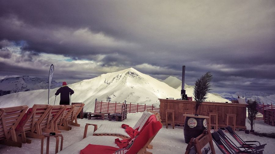 Rear view of man at observation point by snow covered mountain against cloudy sky
