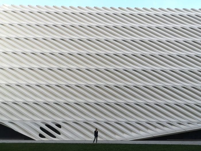 LOW ANGLE VIEW OF MAN WALKING IN CITY AGAINST SKY