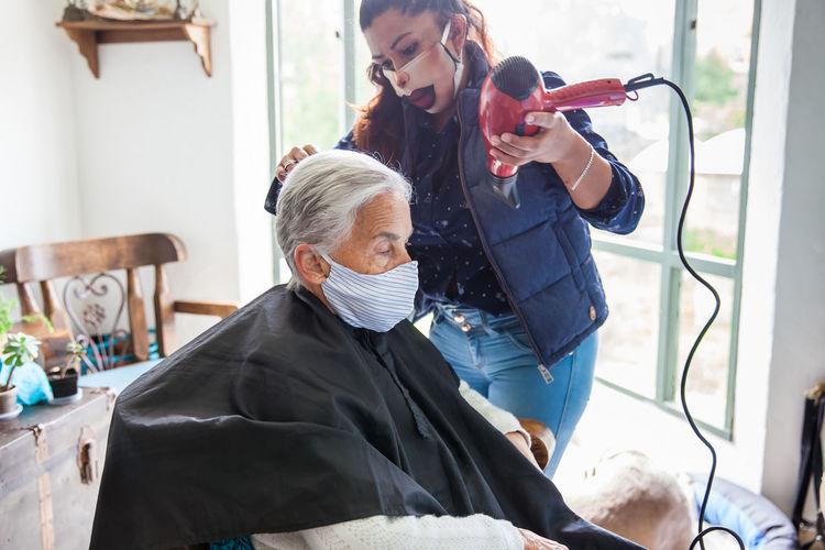Beautician treating hair of customer at home