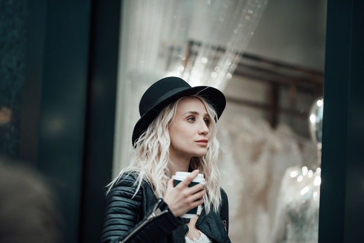 Portrait of young woman using mobile phone at window