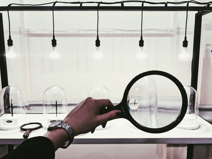 Close-up of hand holding magnifying glass at laboratory