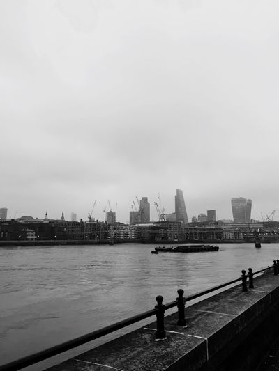 Skyscrapers by thames river against sky