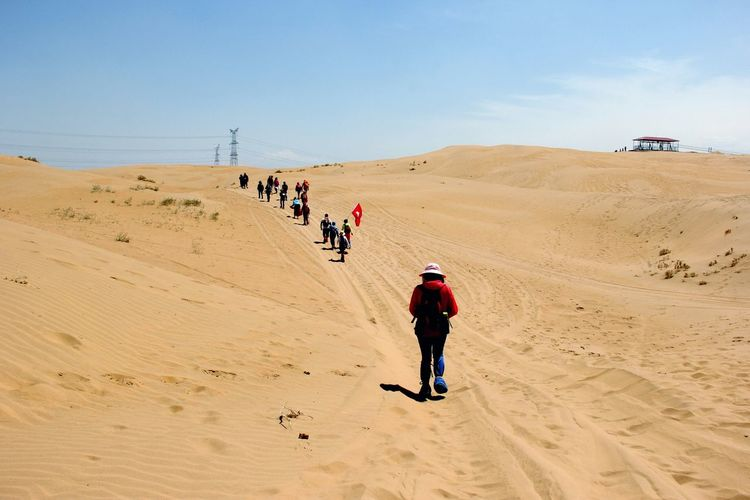 People with flag walking on desert against sky
