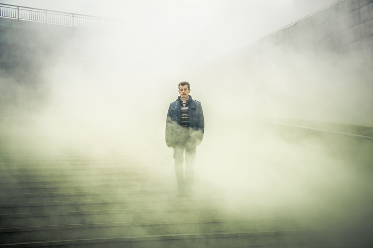 Man standing on steps during foggy weather