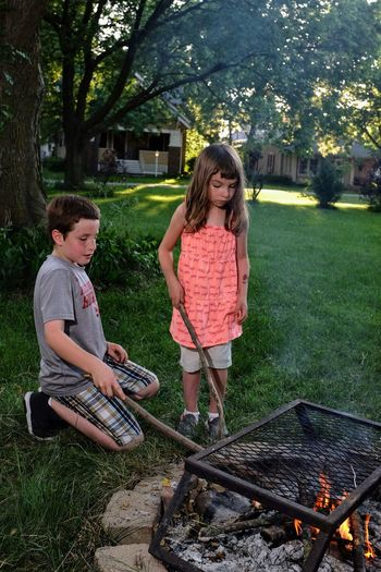 Siblings With Smoke Emitting From Barbecue In Yard