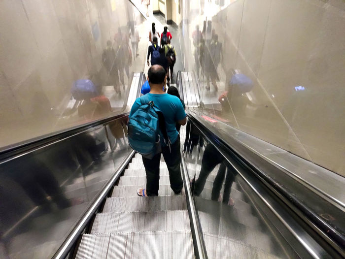 Rear view of people on escalator