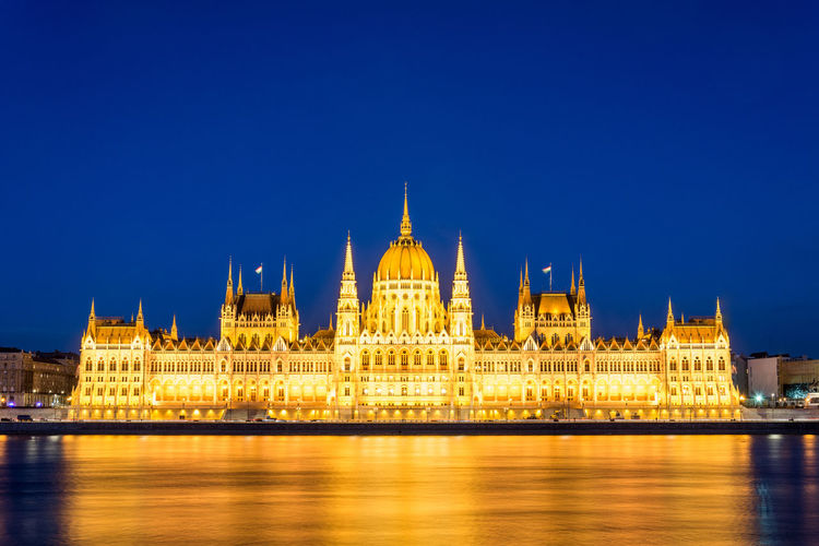 Illuminated Hungarian Parliament Building By Danube River Against Blue Sky
