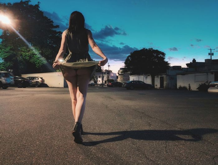 Rear View Of Woman Holding Dress While Walking On Road At Night