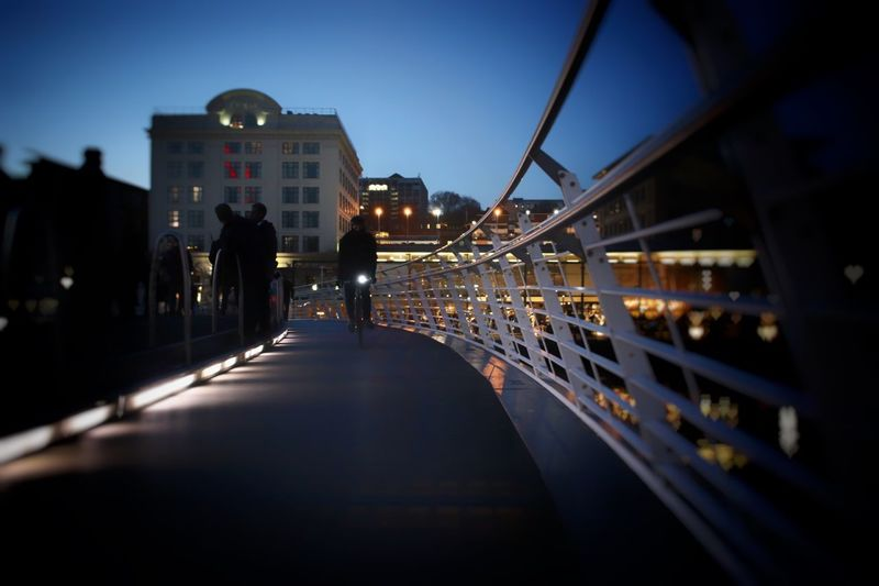 Man Cycling On Illuminated Bridge At Night