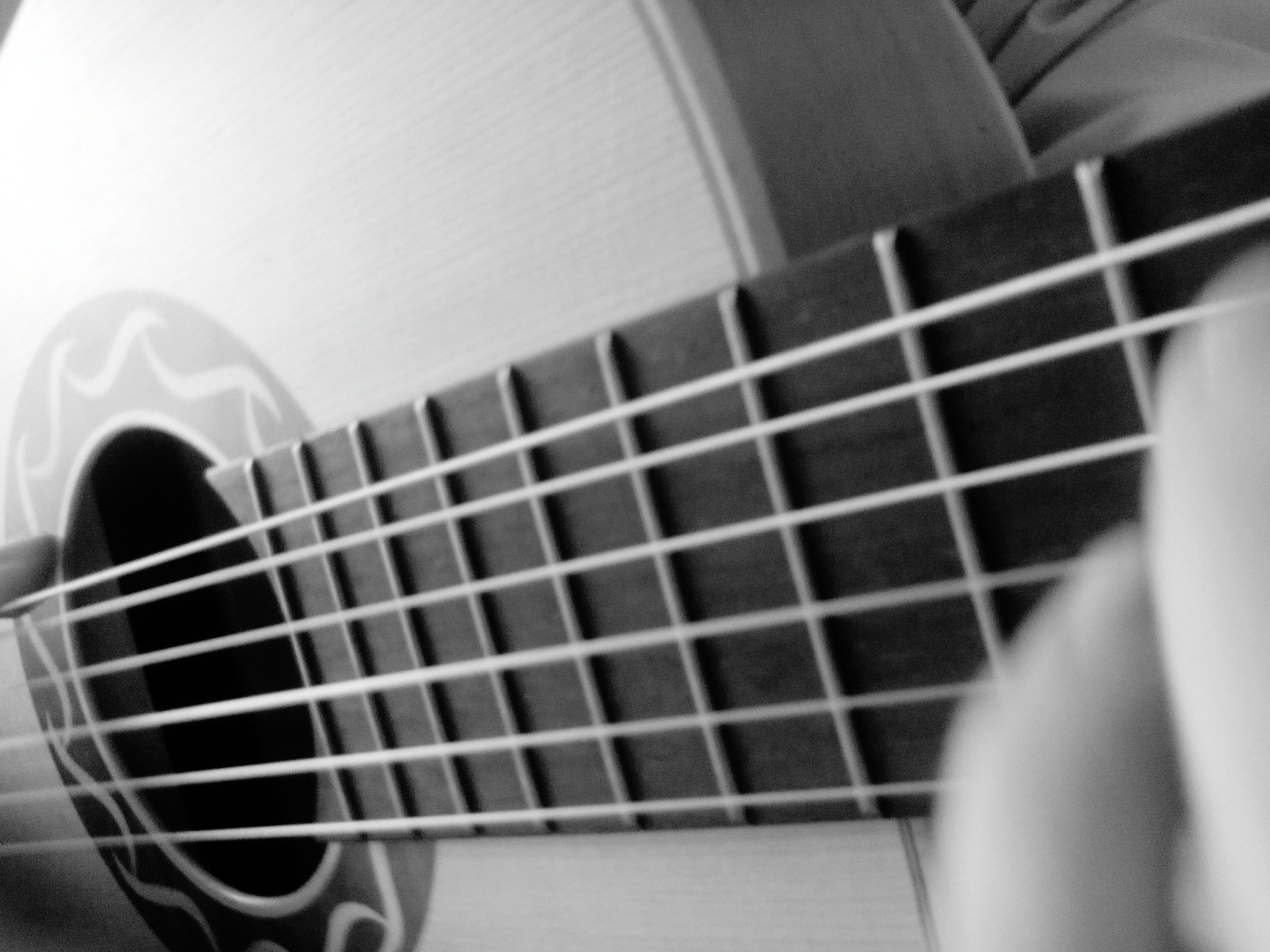 indoors, music, musical instrument, guitar, arts culture and entertainment, musical instrument string, close-up, selective focus, musical equipment, technology, communication, high angle view, focus on foreground, part of, wireless technology, hobbies, lifestyles, men