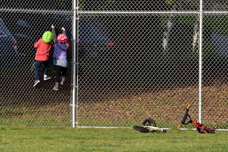 Rear view of siblings climbing on chainlink fence