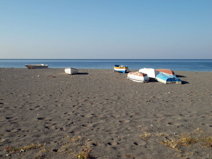 Boats moored at beach against clear sky