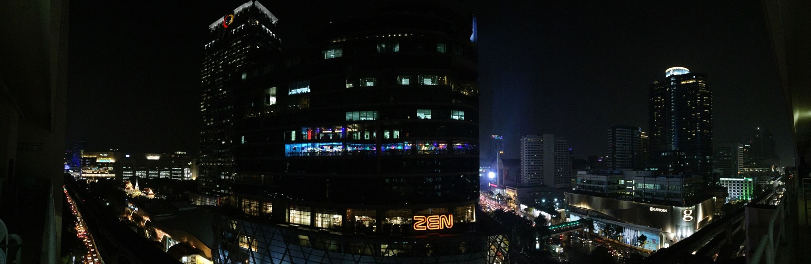 building exterior, night, illuminated, architecture, built structure, city, transportation, street, car, city life, mode of transport, land vehicle, building, street light, city street, road, outdoors, skyscraper, modern, incidental people