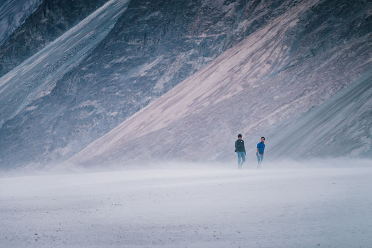 Men standing against mountains during foggy weather