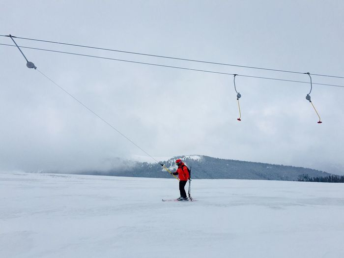 Man Skiing On Snow Covered Mountain Against Sky