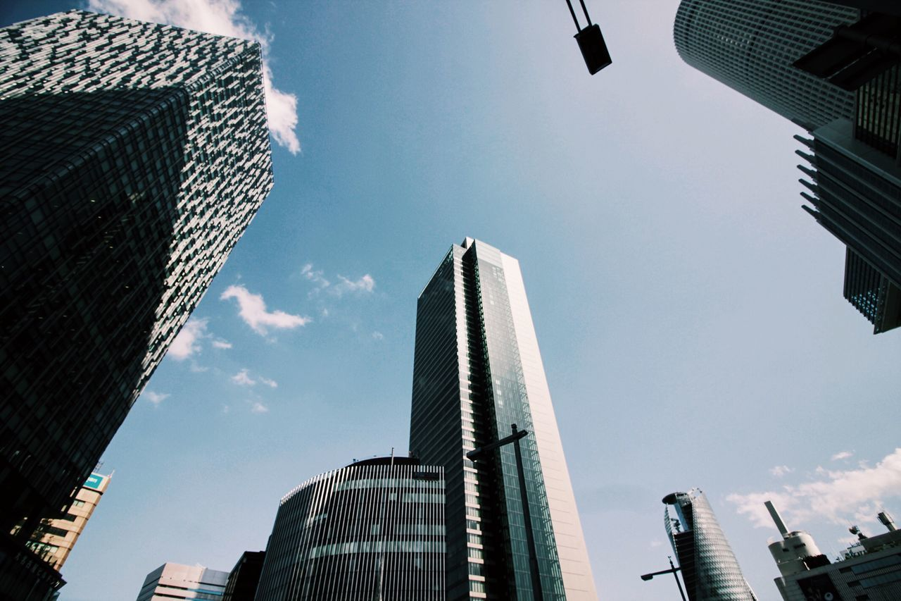 Low angle view of modern buildings in city against sky on sunny day