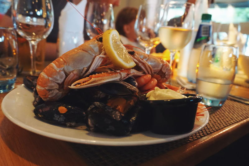 Close-up of seafood served in plate with drinks on table at restaurant