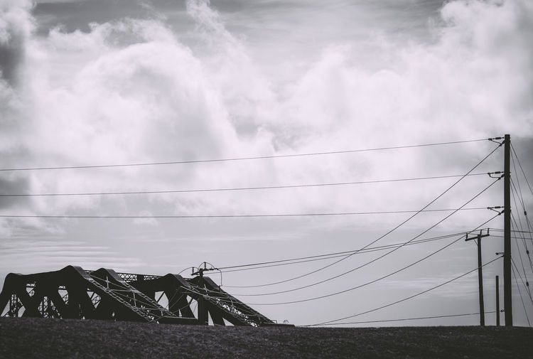 Silhouette of bridge and power lines against cloudy sky
