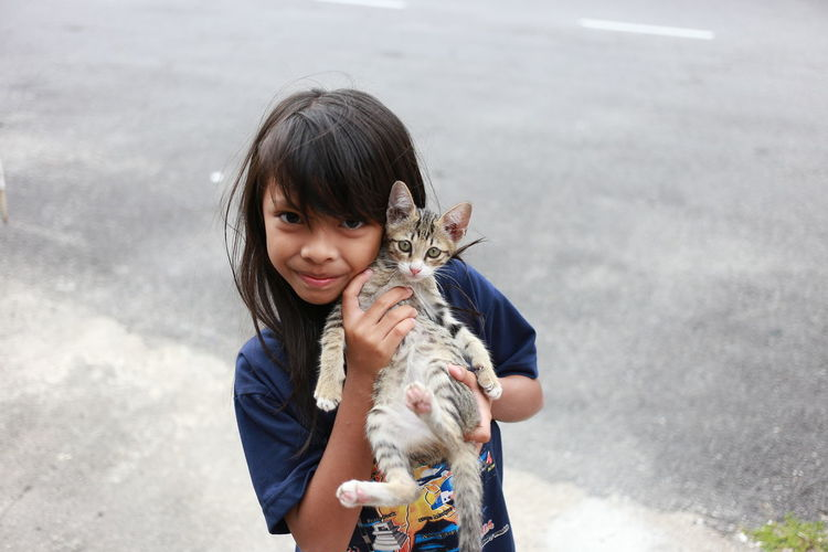 Portrait of girl holding cat while standing on road