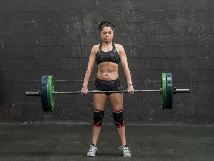 Full length of woman doing deadlift