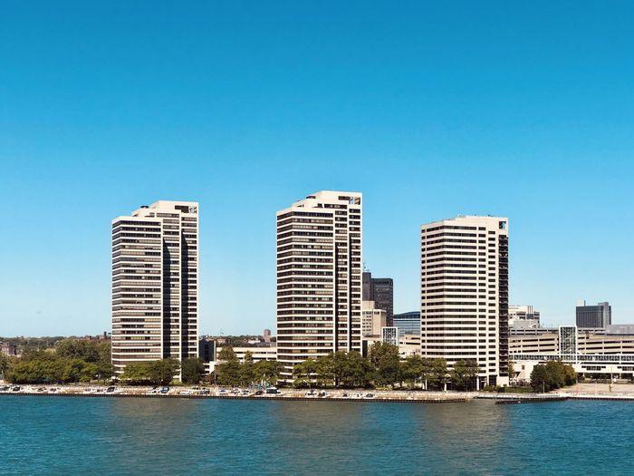 Modern buildings by sea against clear blue sky