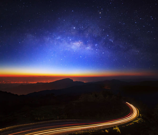 Aerial view of light trails on road against sky at night