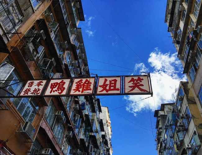 It's worth looking up when exploring Kowloon. HongKong Hong Kong Building Exterior Building Architecture Architectural Detail Blue Sky Sign City Life City Cityscapes Outdoors Information Sign Low Angle View Day Exploring Clouds And Sky Miles Away