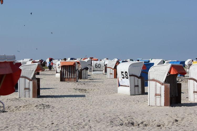 Hooded chairs on beach against clear sky