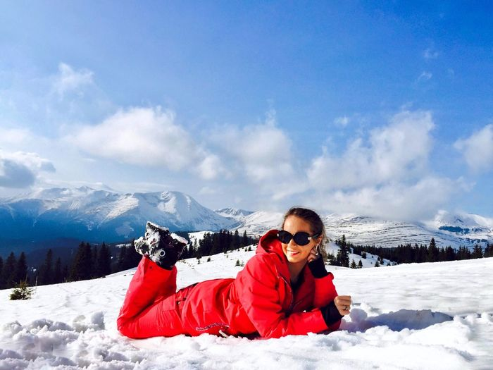Woman in red winter clothes surrounded by snowcapped mountains on a day with blue sky Laying Down Relaxing Blue Sky Snowcapped Mountain Hiking Hiker Scenery Landscape Sunlight Outdoors Day Nature Smiling Woman Snow Winter Cold Temperature Mountain One Person Leisure Activity Mountain Range Real People Sunglasses Warm Clothing Beauty In Nature Vacations Holiday Cloud - Sky Clothing Fashion