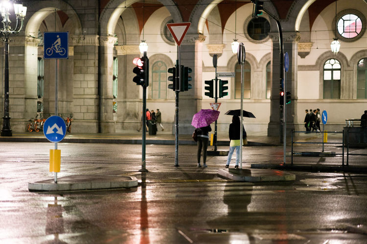 Rainy night in the city of turin Torino Waiting Rain Walking Men Architectural Column Medium Group Of People Wet Sign Outdoors Women People Building Lifestyles Day City Built Structure Reflection Real People Arch Group Of People Architecture Mirkomacaritorino
