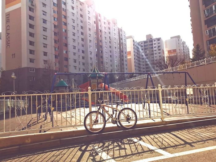 The playground with no children but strong subshine. The bike parked in front makes the area look more lonely. Playground Apartment Daytime Sunshine Bicycle No People