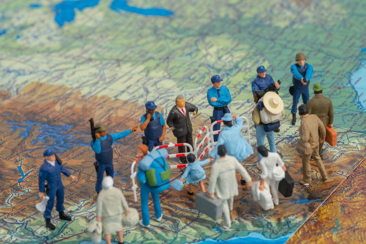 High angle view of figurines standing on map